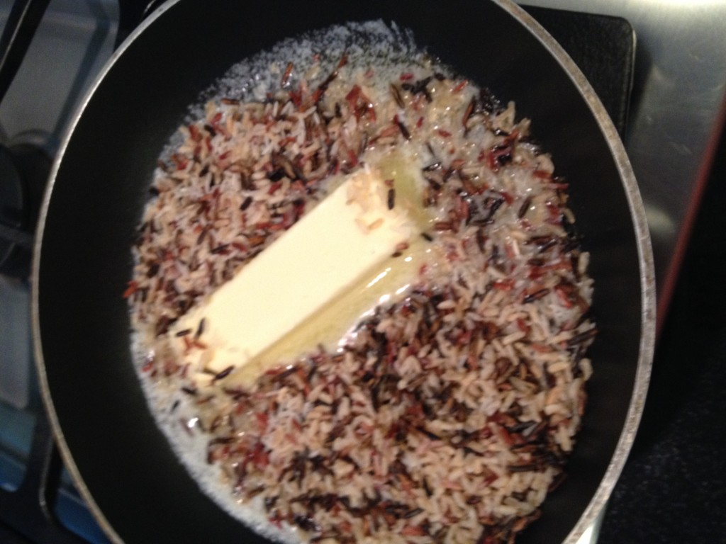 Butter in saute pan with rice added for browning.  Do not add pecans at this point they will get brown.